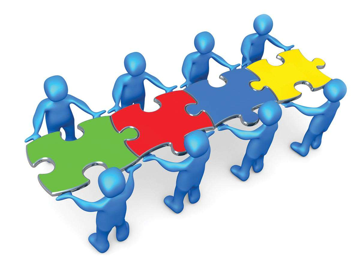 Team Of 8 Blue People Holding Up Connected Pieces To A Colorful
